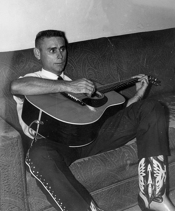 young George Jones playing guitar on couch